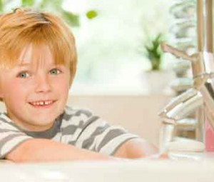 Boy washing hands with soap and water